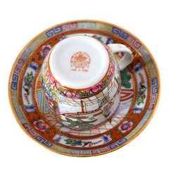 Signed, hand painted china teacup in pinks and blues with gold accents. Features an Asian scene with two women.