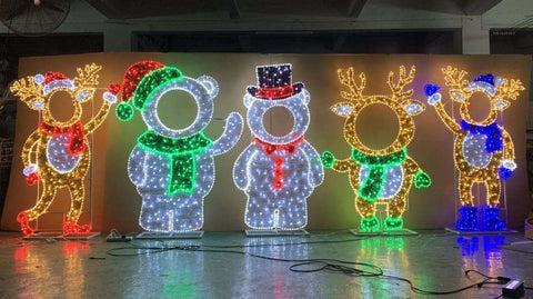 AN image showing 5 different face hole cut outs for christmas time all lite up