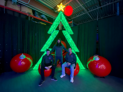The 3 founders of VisiDream Standing in front of their Yuletide holiday seflie station with a large 3d green tree, Christmas ornament chairs and oversized ornaments