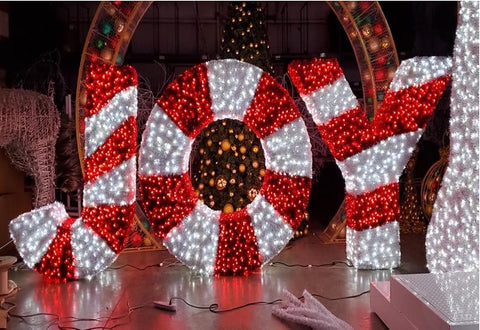 the word joy spelled out in large letter with red and white christmas garland and lights.
