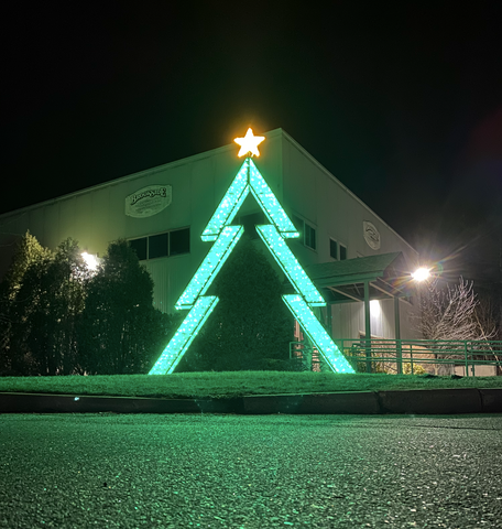 Image of VisiDream oversized green artificial Christmas tree set up outside of an HVAC business