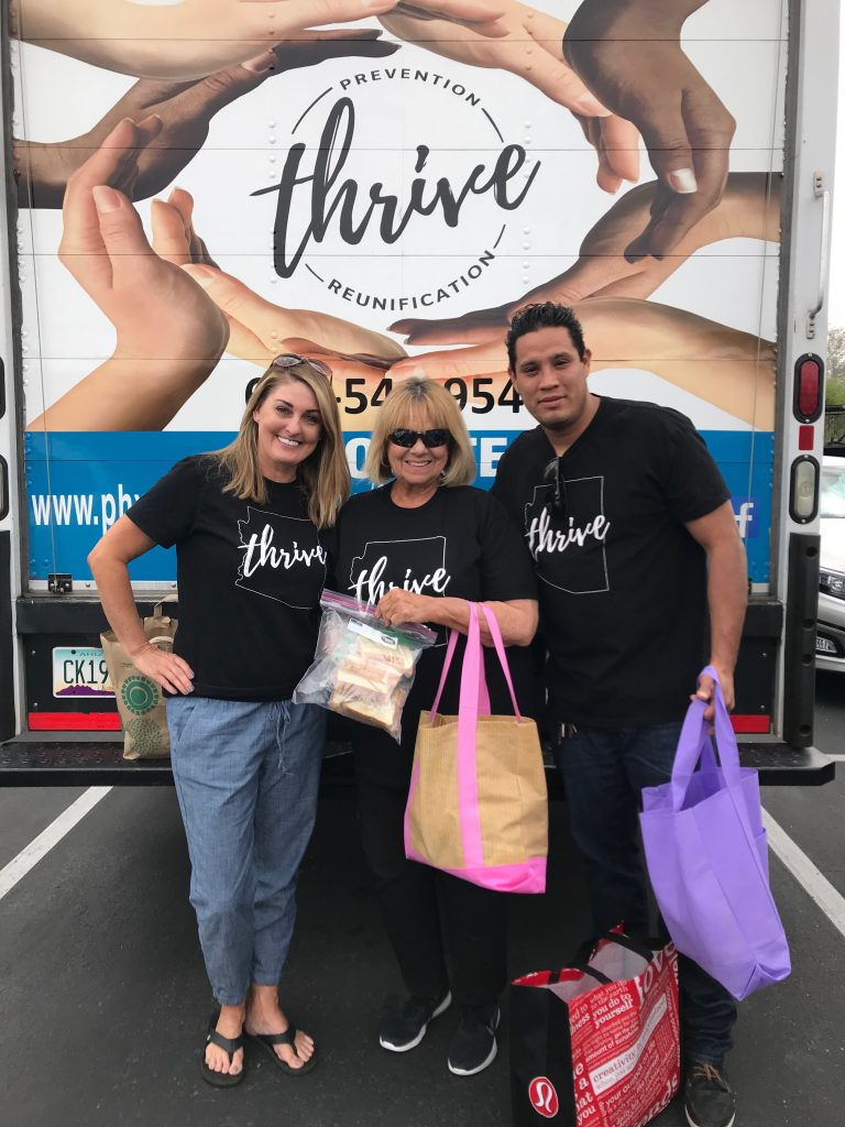 Three Thrive company employees posing in front of delivery truck