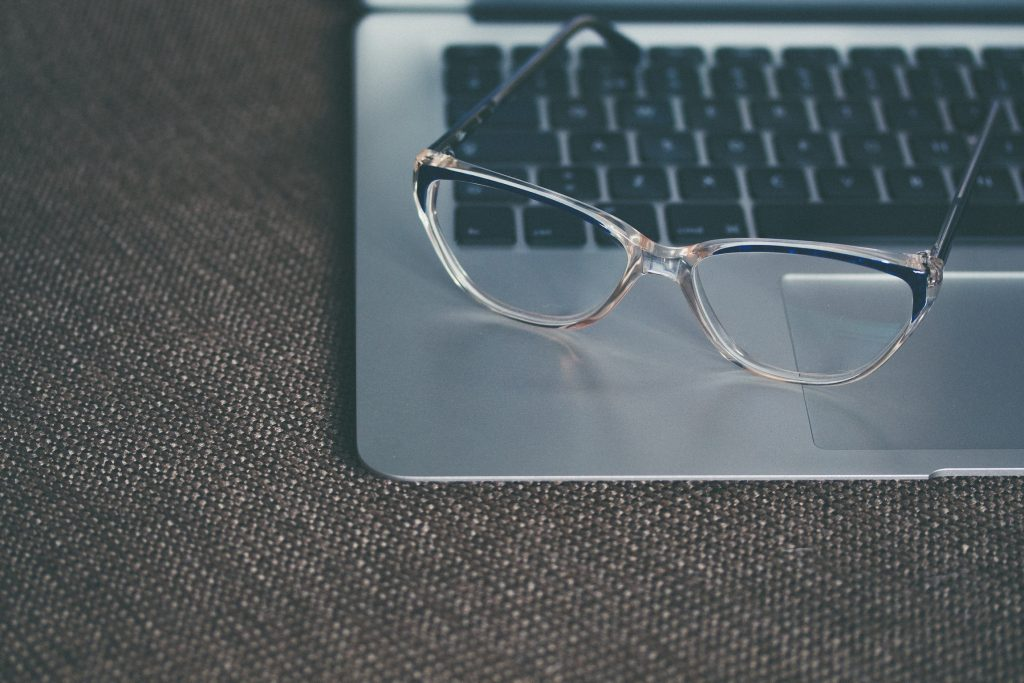 glasses laying on open laptop