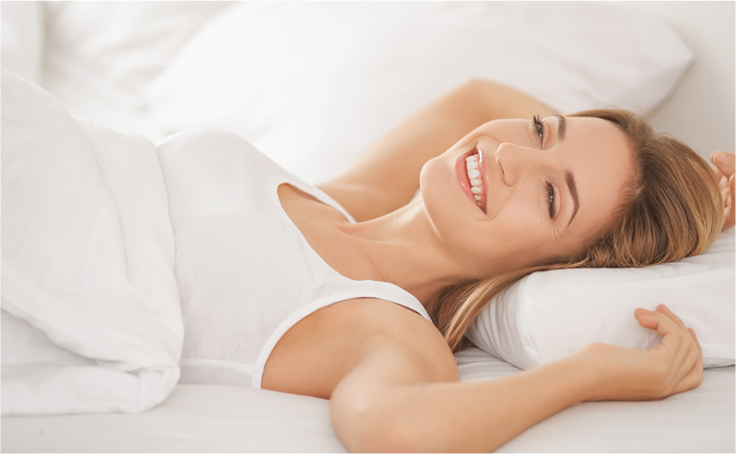 woman laying on back in bed