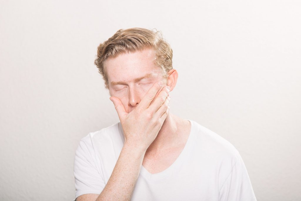 man with eyes closed and hand over face/mouth
