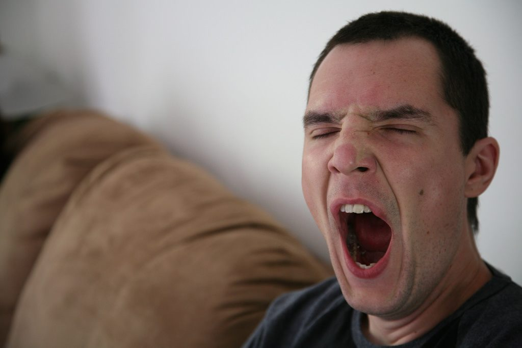 man yawning on couch