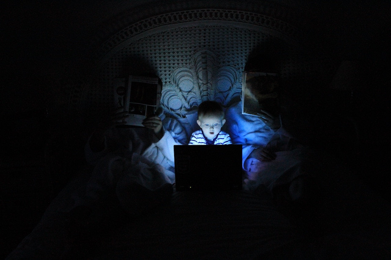 at night, baby on highly lit computer