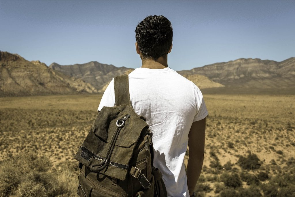 man with backpack looking at desert