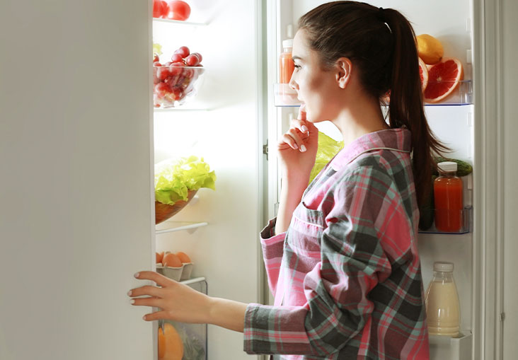 woman standing in front of open fridge thinking