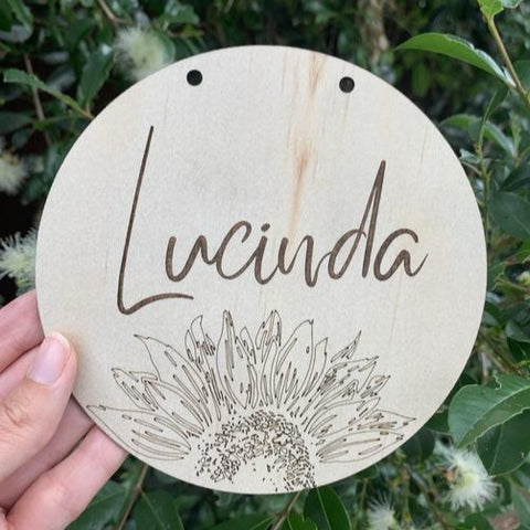 laser cut circular wooden name plaque with sunflower detail