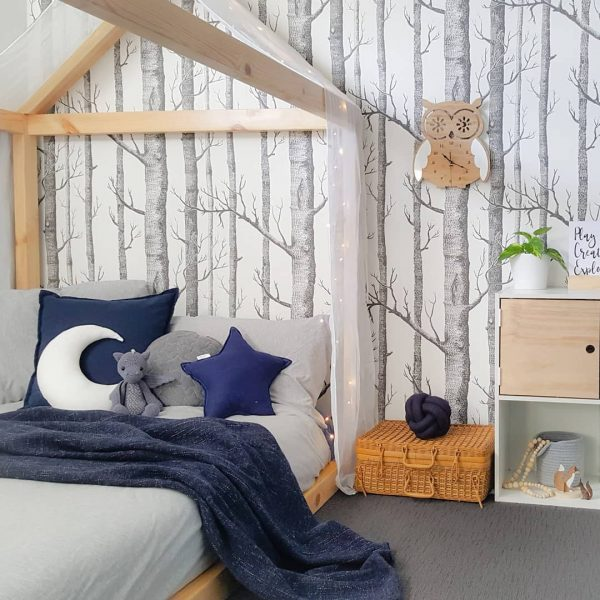 beautiful woodland nursery with blue cushions and own on wall