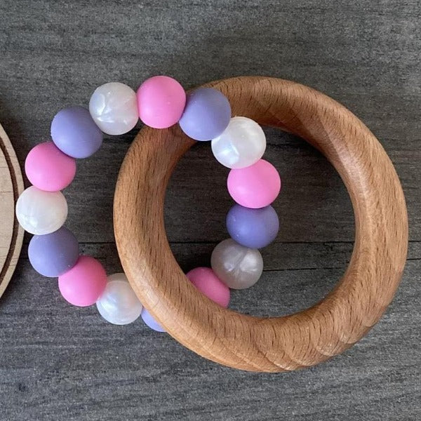 wooden teether ring with bright pink, purple and white silicone beads