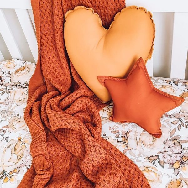rust orange heart and star cushion on cot bed with big throw rug
