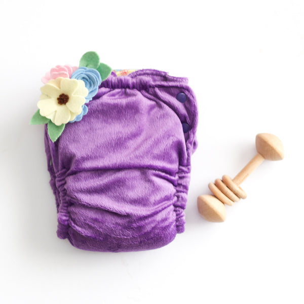 purple minky modern cloth nappy with felt flowers and wooden rattle