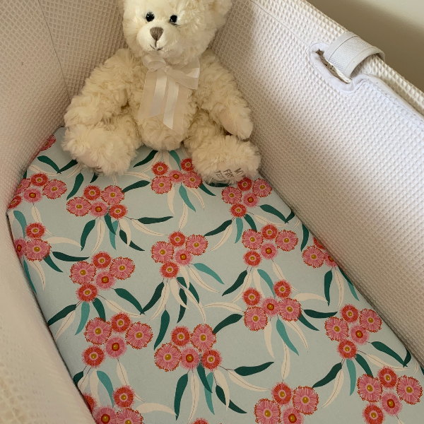 mint bassinet sheet with pink eucalyptus flowers and teddy