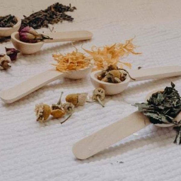 5 wooden spoons with dried flowers and ingredients to make bath salts