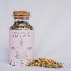 glass bottle filled with botanicals for use as a sitz bath for postpartum women