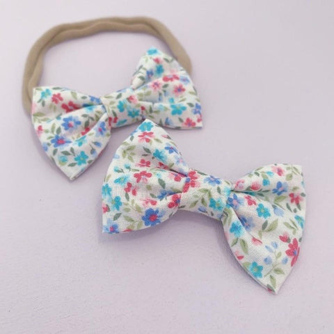 two floral baby bows one with a headband