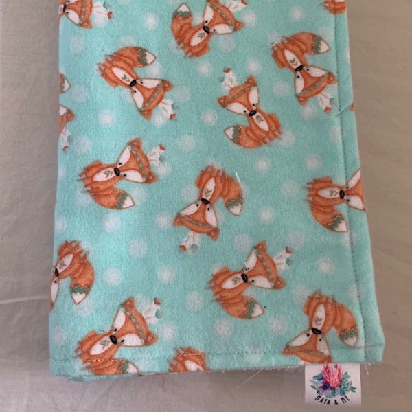 aqua burp cloth with orange foxes wearing feathers in their hair
