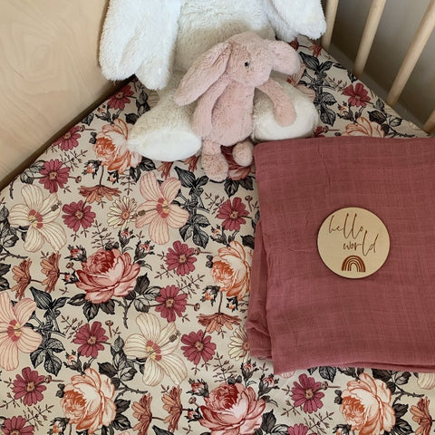 beautiful floral cot sheet with pink and peach flowers, toy bunny and muslin swaddle