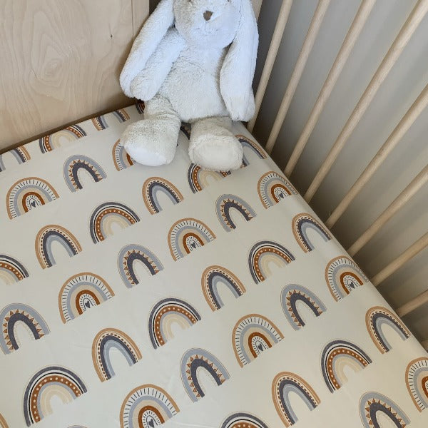 neutral cot sheet with earthy rainbow pattern