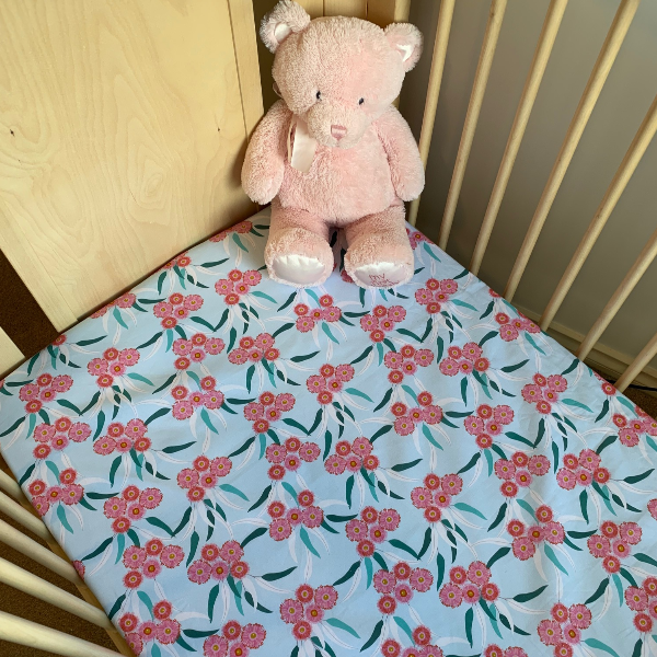 beautiful mint cot sheet with pink eucalyptus flowers and green leaves