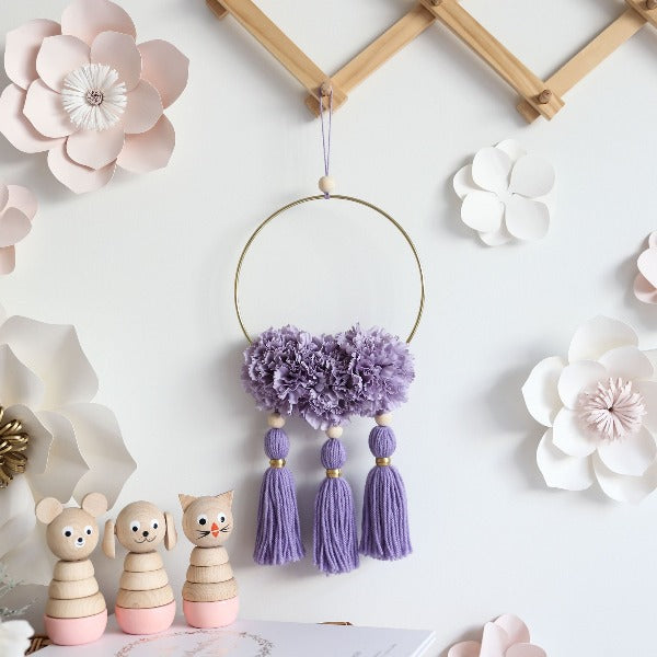 gorgeous nursery wall with hoop that has purple flowers and tassels attached
