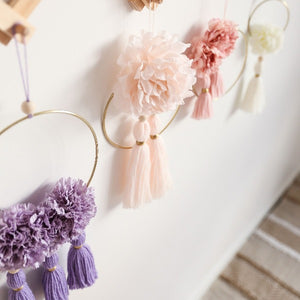 white wall with 4 hoops hanging, flowers and tassels