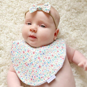 baby girl wearing a blue floral bow and matching bib