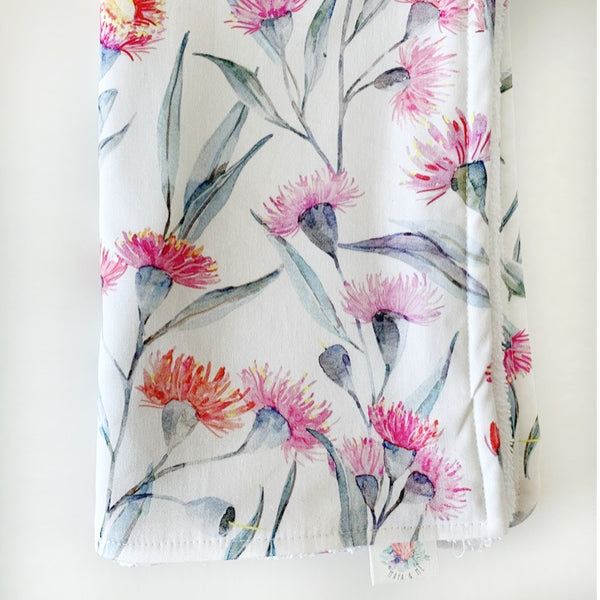 burp cloth that has pink eucalyptus flowers on it