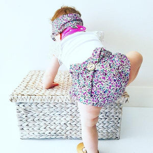 baby wearing purple floral bloomers with button and bow on the back