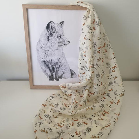 baby muslin swaddle with fox pattern and fox sketch in a frame