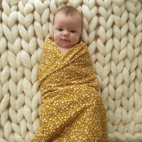 baby wrapped up and swaddled in a floral mustard muslin