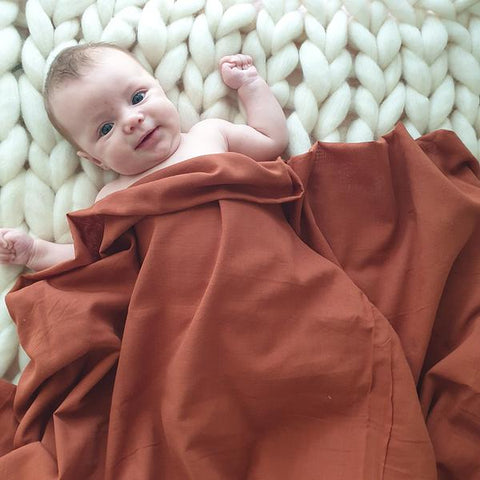 baby laying on a woolly rug with a rust coloured muslin swaddle