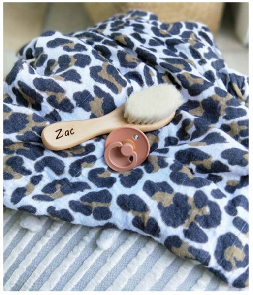 wooden baby brush and baby dummy sittinf on a animal print muslin wrap