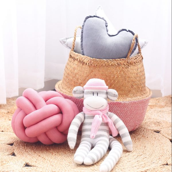 grey heart and pink knot cushion with monkey toy and basket