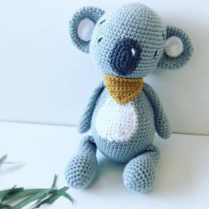 grey crochet koala toy with mustard bandana and big grey nose