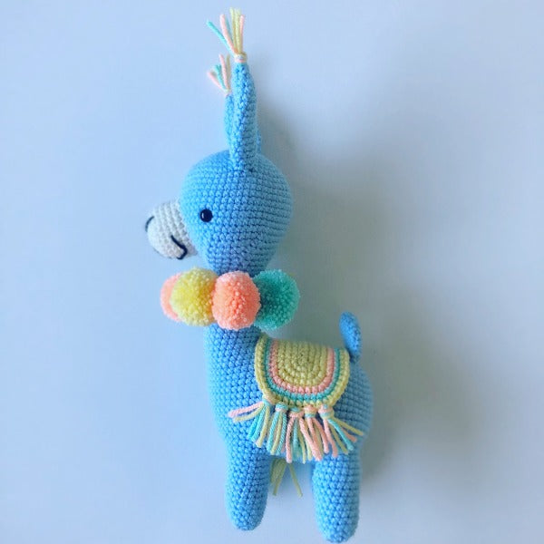 blue crochet llama with festive neon pom poms and saddle
