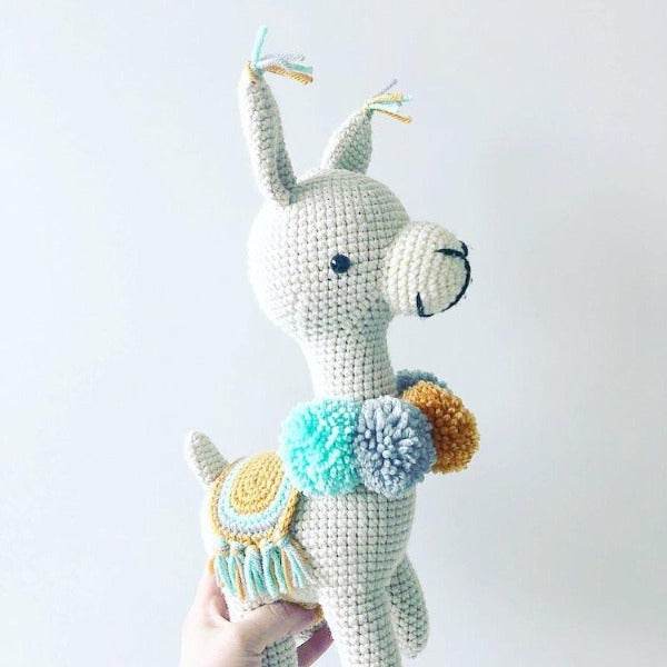 colourful crochet llama with pom poms around its neck and colourful saddle