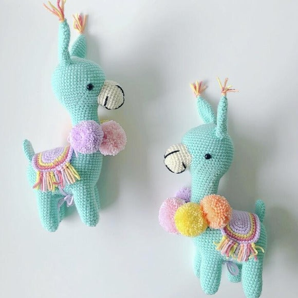 mint green crochet llama toy with orange and lilac pom poms and saddle