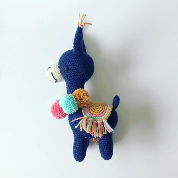 dark navy blue crochet llama with festive green and yellow pom poms and saddle