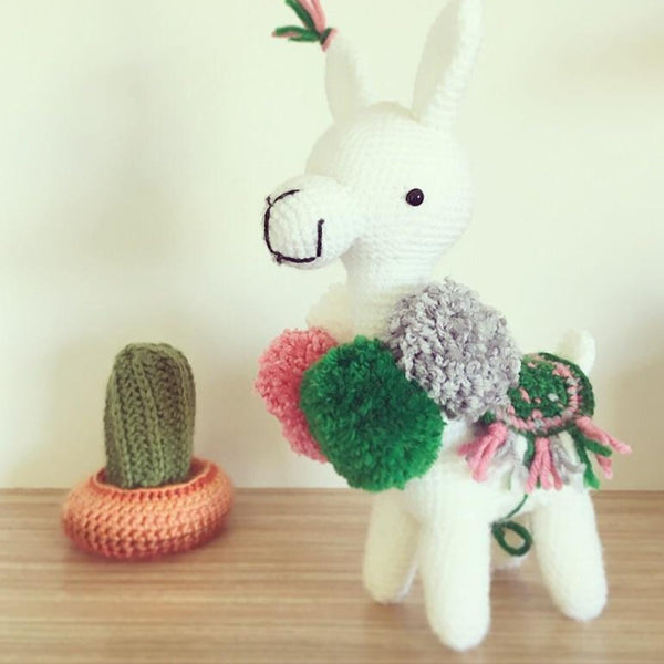 white crochet llama with festive green and pink pom poms and saddle