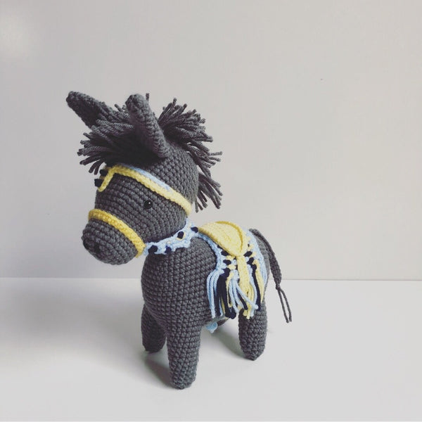 dark grey crochet donley toy with colourful saddle