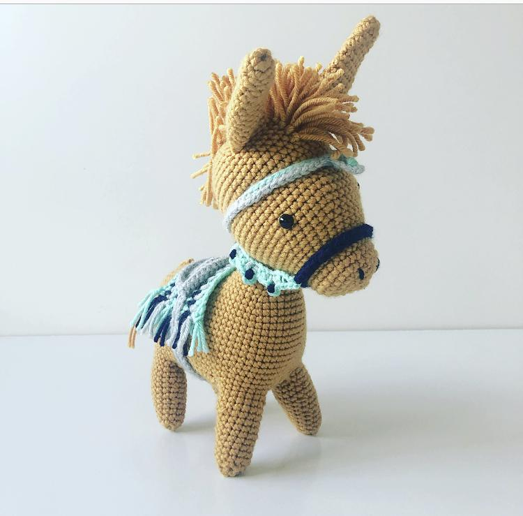 mustard colour crochet donkey toy with colourful saddle