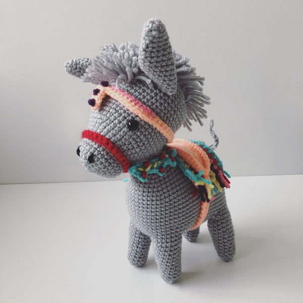 light grey crochet donkey toy with colourful saddle