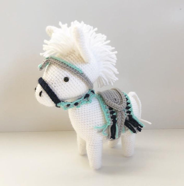 white crochet donkey toy with colourful saddle