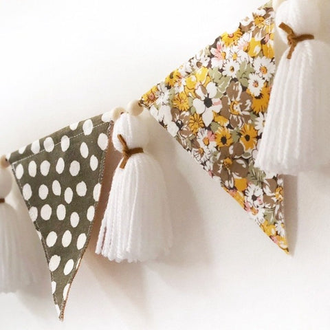 mustard and green floral polka dot bunting with white tassels hanging on the nursery wall