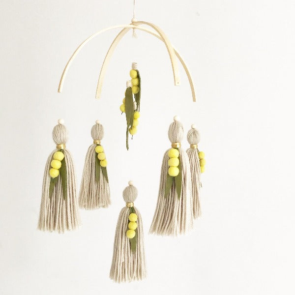 australian wattle themed baby cot mobile hanging from the ceiling with yellow balls and green felt leaves.