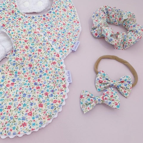 flatlay of baby bibs a scrunchie  and baby bows