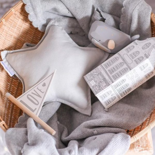 star cushion in a basket with baby toys and blankets